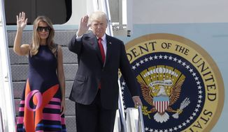 U.S. President Donald Trump and his wife Melania, left, wave, after arriving for the G-20 summit in Hamburg, northern Germany, Thursday, July 6, 2017. The leaders of the group of 20 meet July 7 and 8. (AP Photo/Markus Schreiber)