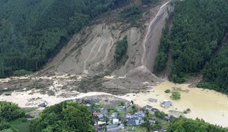 Houses and a road are seen submerged in muddy water after a huge landslide caused by heavy rain hit the Ono district in Hita, Oita prefecture, southwestern Japan Thursday, July 6, 2017. Troops worked Thursday to rescue hundreds of people stranded by flooding in southern Japan. (Nozomu Endo/Kyodo News via AP)