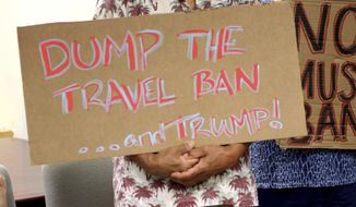 "FILE- In this June 30, 2017, file photo, critics of President Donald Trump's travel ban hold signs during a news conference with Hawaii Attorney General Douglas Chin in Honolulu. A federal judge in Hawaii on Thursday, July 6, left Trump administration rules in place for a travel ban on citizens from six majority-Muslim countries. U.S. District Court Judge Derrick Watson denied an emergency motion filed by Hawaii asking him to clarify what the U.S. Supreme Court meant by a ""bona fide"" relationship in its ruling last month. (AP Photo/Caleb Jones, File)"