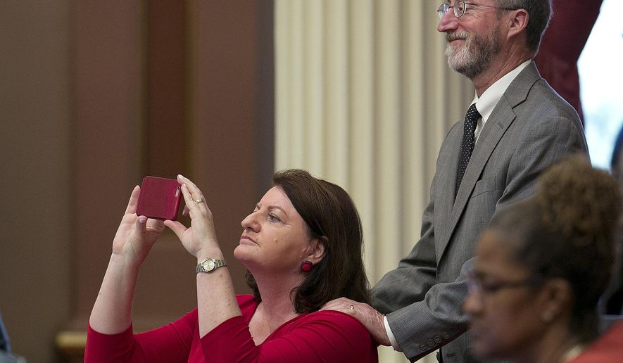 State Sen. Toni Atkins, D-San Diego, snaps a photo as she and Sen. Steve Glazer, D-Orinda, right, watch as the votes are posted for her affordable housing bill, Thursday, July 6, 2017, in Sacramento, Calif. The Senate approved Atkins measure, SB2, that imposes a $75 fee on real estate transaction documents such as deeds and notices with a cap of $225 per transaction. The fee is expected to generate between $200 and $300 million annually for affordable housing projects. The bill now goes to the Assembly. (AP Photo/Rich Pedroncelli)