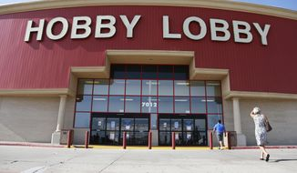 In this June 30, 2014, file photo, customers walk to a Hobby Lobby store in Oklahoma City. Federal prosecutors say Hobby Lobby Stores has agreed to pay a $3 million federal fine and forfeit thousands of ancient Iraqi artifacts smuggled from the Middle East that the government alleges were intentionally mislabled. (AP Photo/Sue Ogrocki, File)
