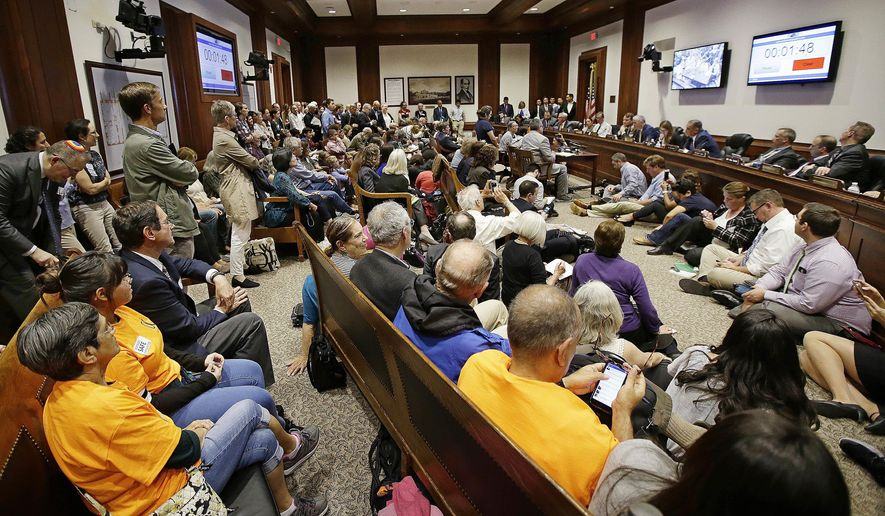 FILE - In this June 9, 2017 file photo, a packed hearing room during a Massachusetts Legislature's Committee on Public Safety and Homeland Security public hearing concerning a bill that calls for sharp limits on cooperation between federal immigration officials and state and local law enforcement agencies, at the Statehouse in Boston. The Justice Department on Thursday, July 6, 2017, questioned whether some so-called sanctuary cities responded honestly when asked whether they follow the law on sharing the citizenship status of people in their custody with federal immigration authorities. (AP Photo/Stephan Savoia, File)