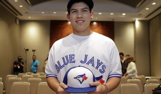 Baseball player Eric Pardinho poses for a picture wearing his new team uniform, after a signing contract in Sao Paulo, Brazil, Thursday, July 6, 2017. Brazil's 16-year-old baseball wonder signed with Toronto Blue Jays. He will spend some time in the Dominican Republic in his initial minor league steps towards Major League Baseball. (AP Photo/Andre Penner)