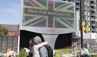 FILE - This is a Tuesday May 23, 2017 file photo of a couple as they embrace under a billboard in Manchester  in England Tuesday May 23, 2017, the day after the suicide attack at an Ariana Grande concert that left more than 20 people dead . British police said Thursday July 6, 2017, that the man who bombed an Ariana Grande concert in Manchester wasn't part of a large network, but other people involved in the attack may still be at large.  (AP Photo/Kirsty Wigglesworth/File)