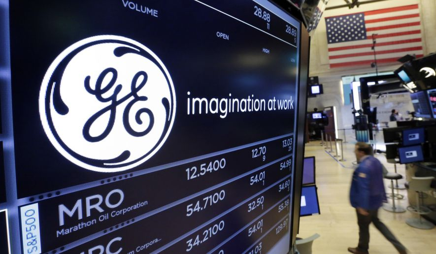 FILE - In this Monday, June 12, 2017, file photograph the General Electric logo appears above a trading post on the floor of the New York Stock Exchange. EU authorities are accusing General Electric, drugmaker Merck and electronics manufacturer Canon of violating European rules to push through mergers or acquisitions. The Commission is not seeking to annul the mergers, but threatening hefty fines if further investigation confirms wrongdoing. (AP Photo/Richard Drew, File)