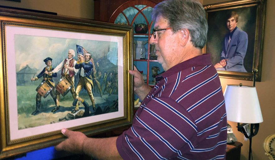 """ADVANCE FOR SATURDAY JULY 8 AND THEREAFTER - In this Wednesday, June 21, 2017 photo, Jay Stevens holds his painting titled """"The Spirit of '76"""", at his home in Port St. Joe, Fla. The painting is believed to be one of the numerous original copies painted by Archibald Willard for the 1876 U.S. Centennial, showing two drummers and a fife player marching with a 13-star U.S. flag, saluting the spirit of the American Revolution.  (Gerald Ensley/The Tallahassee Democrat via AP)"""