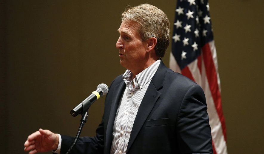 FILE - In this May 30, 2017, file photo, Sen. Jeff Flake, R-Ariz., speaks to members of the Glendale Chamber of Commerce in Glendale, Ariz. Protests against a health care bill in the U.S. Senate heated up Thursday, July 6, when seven opponents of the plan were arrested at Flake's Phoenix and Tucson offices. The protesters were taken into custody as they were trying to sway the Republican's vote on the stalled bill repealing much of former President Barack Obama's health overhaul. (AP Photo/Ross D. Franklin, File)