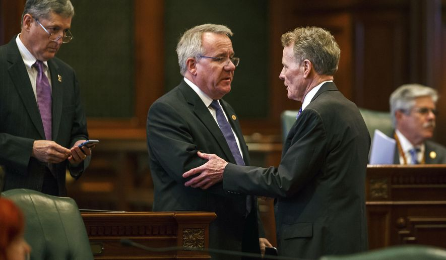 Illinois State Rep. Steve Andersson, R-Geneva, center, shakes hands with Illinois Speaker of the House Michael Madigan, D-Chicago, right, after the Illinois House voted to override Gov. Rauner's veto and pass a budget for the first time in two years during an overtime session at the Illinois State Capitol, Thursday, July 6, 2017, in Springfield, Ill. (Justin L. Fowler /The State Journal-Register via AP)