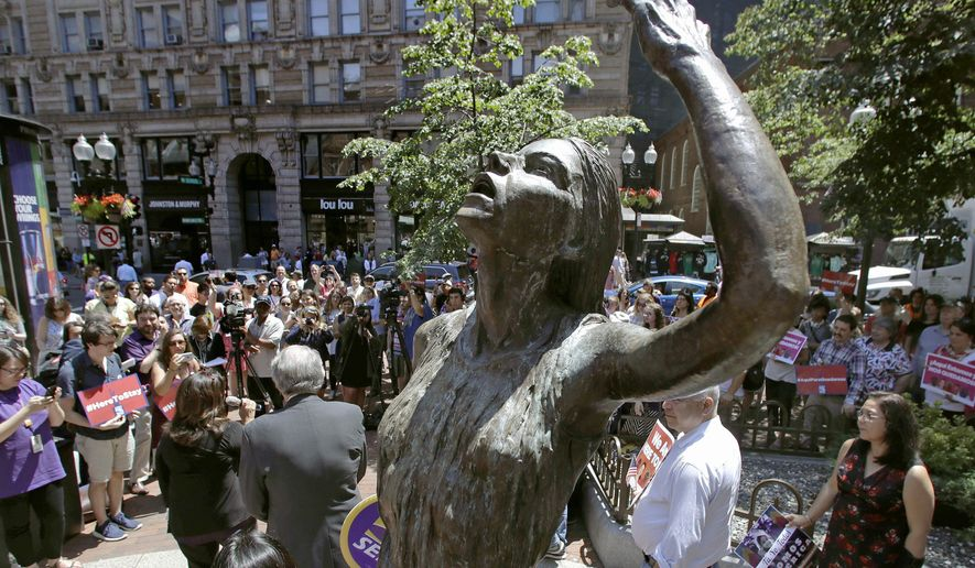 """Immigration activists and labor groups gather around bronze statues during a """"Here to Stay"""" rally at the Irish Famine Memorial in Boston, Thursday, July 6, 2017. Immigration activists and labor groups gathered in Boston in opposition to President Donald Trump's crackdown on illegal immigration. (AP Photo/Charles Krupa)"""