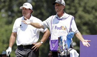 """FILE - In this June 11, 2015, file photo, Phil Mickelson, left, talks with his caddie Jim Mackay on the eighth tee during the first round of the St. Jude Classic golf tournament in Memphis, Tenn. The longtime caddie for Phil Mickelson is going to work for NBC and Golf Channel for the rest of the year. Jim """"Bones"""" Mackay will still be walking golf courses, but with a microphone instead of a 40-pound golf bag. Mackay was the only caddie Mickelson had in his 25-year career. They decided two weeks ago to part ways. (AP Photo/Mark Humphrey, File)"""