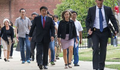 University of Illinois Chief Communications Officer Robin Kaler, center, escorts a contingent including the family of Yingying Zhang, into the Federal Courthouse in Urbana, Ill., before a detention hearing for Brendt Christensen on Wednesday, July 5, 2017. Christensen, the suspect in the kidnapping of the University of Illinois scholar from China, marched in a vigil for the victim a day before his arrest last week, federal prosecutors said Wednesday, adding that he also spoke about what makes an ideal victim and talked about how she fought and resisted. (Robin Scholz/The News-Gazette via AP)