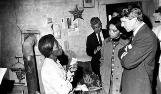 FILE - In this April 11, 1967 file photo, U.S. Sen. Robert F. Kennedy, D-NY, tours the Mississippi Delta near Greenville, Miss., on an anti-poverty investigation. Marian Wright Edelman, second from right, visited poor people in the Mississippi Delta with Kennedy and other U.S. Senators. Edelman returns to Mississippi July 12, 2017, to examine how poverty affects people's lives, much like Sen. Robert F. Kennedy did 50 years ago.  (AP Photo/stf, FILE)
