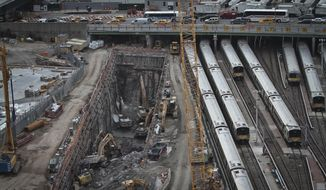 FILE - In this April 17, 2014, file photo, backhoes excavate in a hole reserved for a rail tunnel, left, during the early days of construction at the Hudson Yards redevelopment site on Manhattan's west side in New York. A concrete box was planned inside the project to preserve space for a tunnel from Newark to New York City that would allow it to double rail capacity across the Hudson River. An environmental study has been released for the Hudson River rail tunnel project, amid concerns the effort could lose key federal funding under President Donald Trump's proposed budget. (AP Photo/Bebeto Matthews, File)