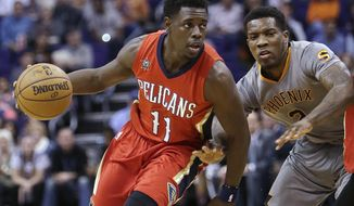 FILE - In this Feb. 13, 2017, file photo, New Orleans Pelicans guard Jrue Holiday (11) drives on Phoenix Suns guard Eric Bledsoe  during an NBA basketball game in Phoenix. Holiday went into this offseason as an unrestricted free agent, but decided to stick with New Orleans, where he has played the past four seasons. Holiday says he hopes his decision influences Pelicans All-Star center DeMarcus Cousins, who has one season left on his contract. (AP Photo/Rick Scuteri, File)