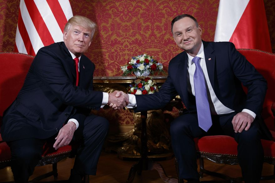 U.S. President Donald Trump, left, and Polish President Andrzej Duda pose for photographers as they shake hands during their meeting at the Royal Castle, Thursday, July 6, 2017, in Warsaw. (AP Photo/Evan Vucci)