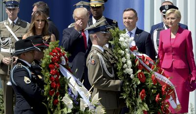 Soldiers carry wreaths as U.S. President Donald Trump, Poland's President Andrzej Duda, U.S. First Lady Melania Trump, left and Poland's first lady Agata Kornhauser-Duda, right, stand, in Krasinski Square, in Warsaw, Poland, Thursday, July 6, 2017.(AP Photo/Alik Keplicz)