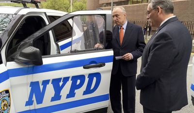 In this May 10, 2016 photo provided by the New York City Police Department, NYPD Commissioner William Bratton, second from right, examines a bullet resistant safety shield affixed to the side window of an NYPD patrol car in New York. After two officers were fatally gunned down through the window of their squad car in 2014, the city embarked on plan to outfit all of its squad cars with inch-thick bullet-resistant glass and armored door panels. That plan did not cover RV-like mobile command posts, like the one Officer Miosotis Familia sat inside when she was fatally shot while on duty in the early hours of Wednesday, June 5, 2017. (NYPD via AP)