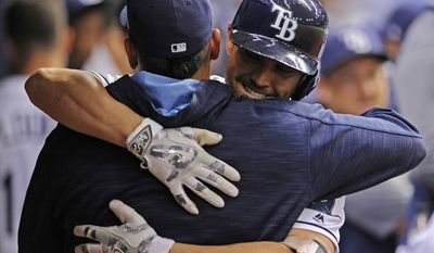 Tampa Bay Rays' Jesus Sucre, left, hugs Peter Bourjos in the dugout after Bourjos' solo home run off Boston Red Sox starter Chris Sale during the fifth inning of a baseball game Thursday, July 6, 2017, in St. Petersburg, Fla. (AP Photo/Steve Nesius)