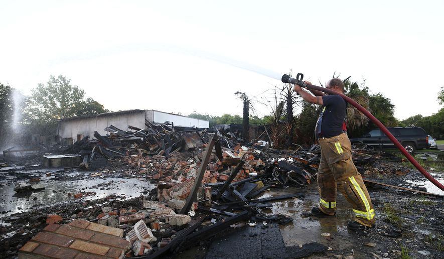 South Houston volunteer firefighter Robert Kyle douses hot spots remaining from a two-alarm fire that destroyed a two-story warehouse on North 1st Street near Spencer Highway Thursday, July 6, 2017, in South Houston. The flames from the fire blew out a transformer, leaving people in the area without power. (Godofredo A. Vasquez/Houston Chronicle via AP)
