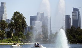 People in pedal-powered boats take advantage of a breeze creating cooling spray from fountains in Echo Park Lake near downtown Los Angeles, Thursday, July 6, 2017. A heat wave blanketing the U.S. Southwest has toppled temperature records, raised wildfire danger and sent residents to pools, beaches and even fountains for cool relief. Officials warned people to avoid strenuous activity during the day on Friday, when the worst heat was expected across Southern California. (AP Photo/Reed Saxon)