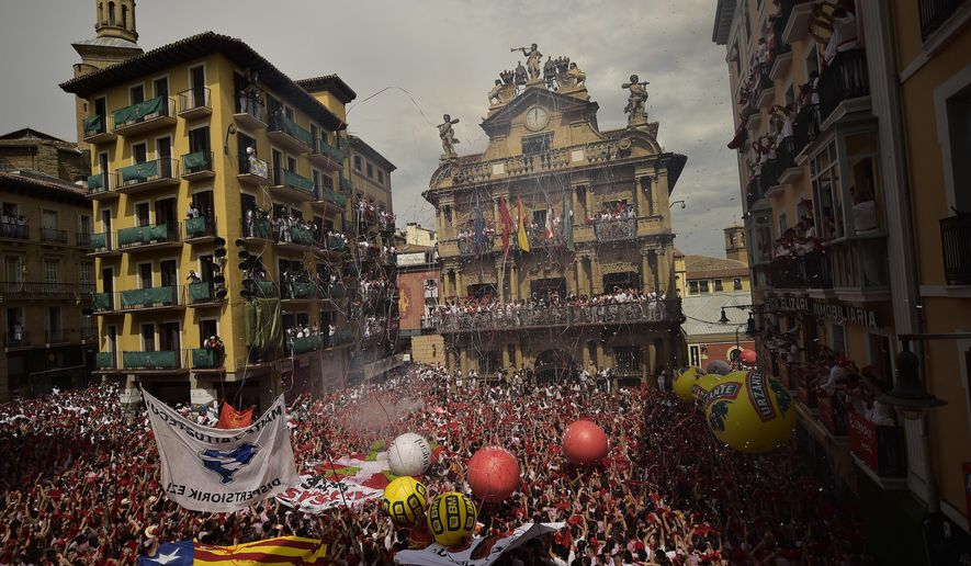 People celebrate during the launch of the 'Chupinazo' rocket, to celebrate the official opening of the 2017 San Fermin Fiestas, in Pamplona, northern Spain, Thursday, July 6, 2017. Revelers from around the world kick off the festival with a messy party in the Pamplona town square, one day before the first of eight days of the running of the bulls. (AP Photo/Alvaro Barrientos)