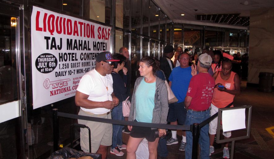 Gerald Winchester, left, chats with Marie Marine, right, as they wait to enter the former Trump Taj Mahal casino in Atlantic City N.J. on Thursday July 6, 2017 for a sale of the casino hotel's contents. Included in the items for sale were crystal chandeliers from Austria that now-President Donald Trump bought for the casino when he opened it in 1990. The casino shut down last year under different ownership. (AP Photo/Wayne Parry)