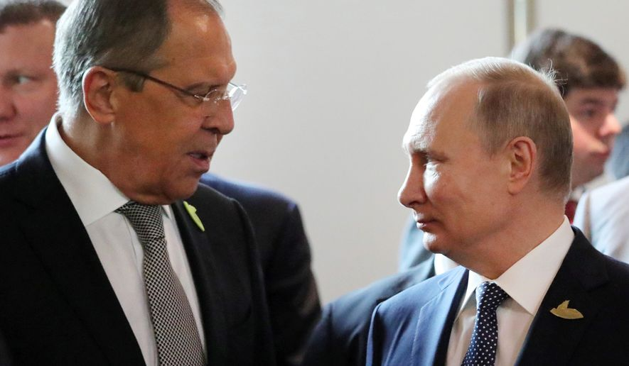 Russian President Vladimir Putin, right, and Foreign Minister Sergey Lavrov talk to each other as they arrive to attend the first day of the G-20 summit in Hamburg, northern Germany, Friday, July 7, 2017. The leaders of the group of 20 meet July 7 and 8. (Mikhail Klimentyev/Pool Photo via AP)