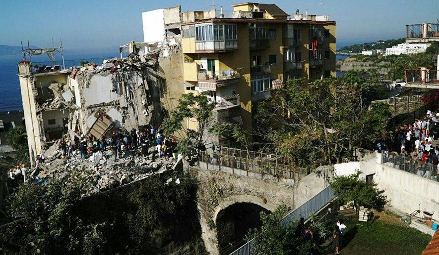 Rescuers work amid the rubble of a building that collapsed, left, in Torre Annunziata, near Naples, southern Italy, Friday, July 7, 2017. A five-story apartment block collapsed early Friday near the southern Italian city of Naples, and authorities were digging by hand to find anyone who may have been trapped. (Ciro Fusco/ANSA via AP)