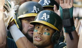Oakland Athletics' Khris Davis is greeted in the dugout after he hit a three-run home run against the Seattle Mariners during the fifth inning of a baseball game, Thursday, July 6, 2017, in Seattle. (AP Photo/Ted S. Warren)