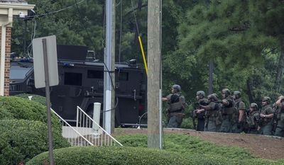 "Police officers move toward a Wells Fargo Bank, Friday, July 7, 2017 in Marietta, Ga. A man who claimed to have a bomb that could ""take out the room"" barricaded himself inside a suburban Atlanta bank Friday, sparking an hours-long standoff that forced police to bust through a brick wall of the building and later ended with the suspect's death. (AP Photo/Mike Stewart)"