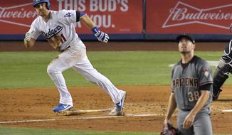 Los Angeles Dodgers' Logan Forsythe, left, watches his solo home run off Arizona Diamondbacks starting pitcher Robbie Ray, right, during the fifth inning of a baseball game, Thursday, July 6, 2017, in Los Angeles. (AP Photo/Mark J. Terrill)