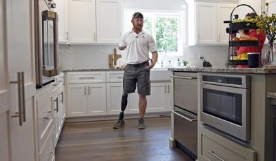 """In this June 29, 2017 photo, retired U.S. Army Sgt. 1st Class Jared Bullock describes some  of the modifications of the kitchen during a tour of his family's new smart home provided through the Gary Sinise Foundation following a dedication ceremony, outside of Carbondale, Ill. Bullock lost his right arm and right leg to an improvised explosive device in Afghanistan in 2013. The foundation established by Gary Sinise, an actor best known for his portrayal of Lt. Dan in the 1994 film """"Forrest Gump"""", donates such homes to wounded veterans. (Byron Hetzler/The Southern, via AP)"""