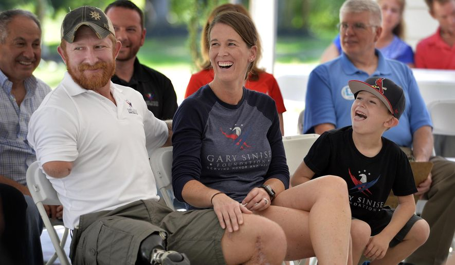 """In this June 29, 2017 photo, retired U.S. Army Sgt. 1st Class Jared Bullock, left, his wife,  Jesica, and son, Aidan, enjoy a laugh during the dedication ceremony for their new specially adapted smart home built through the Gary Sinise Foundation outside of Carbondale, Ill. Bullock lost his right arm and right leg to an improvised explosive device in Afghanistan in 2013. The foundation established by Gary Sinise, an actor best known for his portrayal of Lt. Dan in the 1994 film """"Forrest Gump"""", donates such homes to wounded veterans. (Byron Hetzler/The Southern, via AP)"""