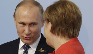 Russian President Vladimir Putin, left, is welcomed by German Chancellor Angela Merkel on the first day of the G-20 summit in Hamburg, northern Germany, Friday, July 7, 2017. The leaders of the group of 20 meet July 7 and 8. (AP Photo/Michael Sohn)