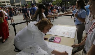 """Carolyn Donnell signs a """"Get Well"""" card for Cleveland Indians manager Terry Francona before a baseball game between the Detroit Tigers and the Indians, Friday, July 7, 2017, in Cleveland. Francona underwent a procedure Thursday to correct an irregular heartbeat that sidelined him for a few games and will prevent him from managing in the All-Star Game next week.(AP Photo/Tony Dejak)"""