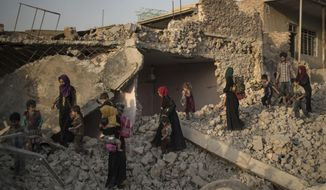 Iraqi civilians flee through the rubble of destroyed houses in the Old City of Mosul, Iraq, Tuesday, July 4, 2017. As Iraqi forces continued to advance on the last few hundred square kilometers of Mosul held by the Islamic State group, the country's Prime Minister said Tuesday the gains show Iraqis reject terrorism. (AP Photo/Felipe Dana)