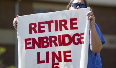 Lauren Sargent, of Ann Arbor, Mich. takes part in a protest before the Enbridge Line 5 pipeline public information session at Holt High School on Thursday, July 6, 2017 in Holt, Mich. The report by Dynamic Risk Assessment Systems, Inc. was prepared independently for the state of Michigan. (Cory Morse/The Grand Rapids Press via AP)