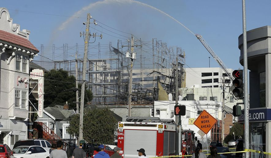 Firefighters spray a building in Oakland, Calif., Friday, July 7, 2017. A huge fire at the building under construction in Oakland has been contained early Friday, but evacuations remain in place at nearby buildings. (AP Photo/Jeff Chiu)