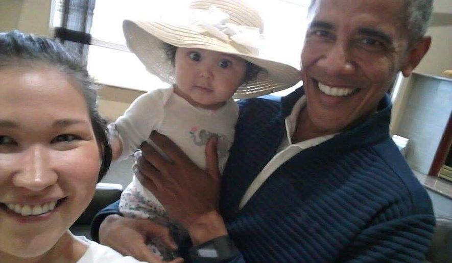 "In this July 3, 2017 photo provided by Jolene Jackinsky, former U.S. President Barack Obama holds Jackinsky's 6-month-old baby girl while posing for a selfie with the pair at a waiting area at Anchorage International Airport, in Anchorage, Alaska. Jackinsky said Obama walked up to her and asked, ""Who is this pretty girl?"" (Jolene Jackinsky via AP)"