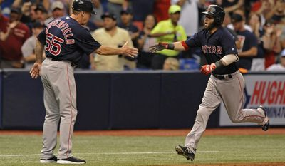 Boston Red Sox third base coach Brian Butterfield, left, congratulates Dustin Pedroia who hit a two-run home run off Tampa Bay Rays starter Jake Odorizzi during the third inning of a baseball game Friday, July 7, 2017, in St. Petersburg, Fla. (AP Photo/Steve Nesius)