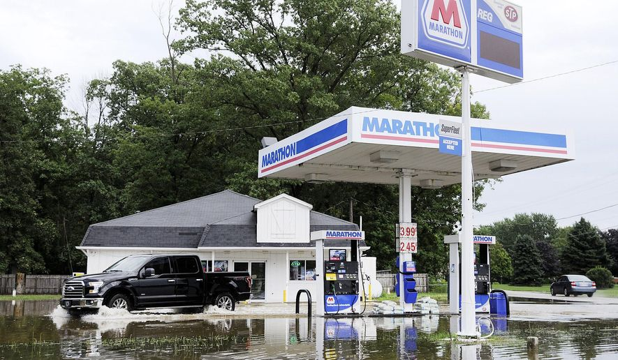 A truck drives through the flooded Marathon station at Indiana 67 and County Road 100 South in Madison County Ind. after heavy rain on Thursday, July 6, 2017. Several roads were covered by high water in Union Township after 3 inches of rain fell in the area around Chesterfield Ind. according to the Madison County Emergency Management Agency. (Don Knight/The Herald-Bulletin via AP)
