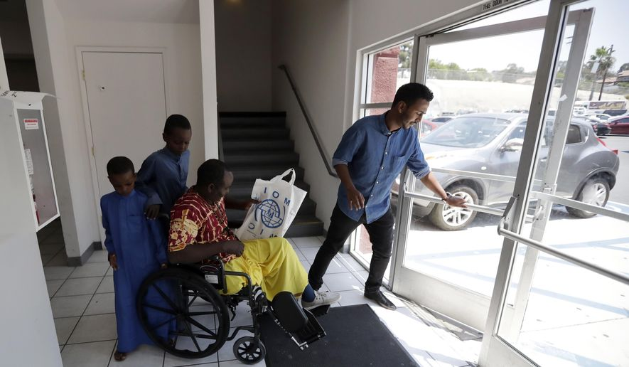 Ali Said, of Somalia, center, leaves a center for refugees with his two sons, as refugee caseworker Mohamed Yassin, right, holds open the door Thursday, July 6, 2017, in San Diego. Said, whose leg was blown off by a grenade, says he feels unbelievably lucky to be among the last refugees allowed into the United States before stricter rules kick in as part of the Trump administration's travel ban. (AP Photo/Gregory Bull)