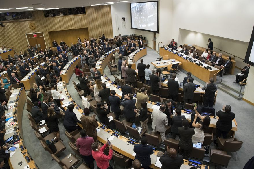 Delegates give a standing ovation after a vote by the conference to adopt a legally binding instrument to prohibit nuclear weapons, leading towards their total elimination, Friday, July 7, 2017 at United Nations headquarters. More than 120 countries have approved the first-ever treaty banning nuclear weapons at a U.N. meeting boycotted by all nuclear-armed nations. Friday's vote was 122 countries in favor with the Netherlands opposed and Singapore abstaining.(AP Photo/Mary Altaffer)