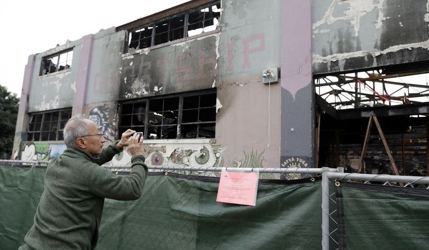 ** HOLD FOR OVERNIGHT MOVEMENT ** FILE - In this Dec. 13, 2016 file photo, a man takes cell phone photos at the scene of a warehouse fire in Oakland , Calif. The man blamed for the nation's deadliest structure fire in more than 14 years will be arraigned in Northern California on 36 counts of involuntary manslaughter. Derick Almena is scheduled to enter a plea Thursday, June 8, 2017. The 47-year-old was arrested and charged Monday with creating a deadly firetrap by illegally converting an Oakland warehouse into a party space and housing. (AP Photo/Marcio Jose Sanchez, File)