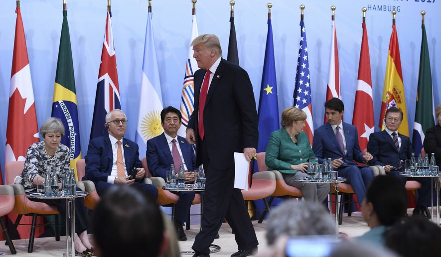 """US President Donald Trump, center, wlks to the desk to deliver a speech during the panel discussion """"Launch Event Women's Entrepreneur Finance Initiative"""" on the second day of the G-20 summit in Hamburg, Germany, Saturday, July 8, 2017. (Patrik Stollarz/Pool Photo via AP)"""