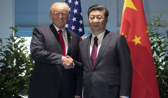 US President Donald Trump and Chinese President Xi Jinping, right, shake hands as they arrive for a meeting on the sidelines of the G-20 Summit in Hamburg, Germany, Saturday, July 8, 2017.  (Saul Loeb/Pool Photo via AP)