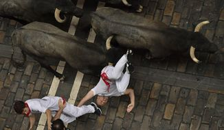A revellers falls in front of Jose Escolar fighting bulls during the second running of the bulls at the San Fermin Festival, in Pamplona, northern Spain, Saturday, July 8, 2017. Revellers from around the world flock to Pamplona every year to take part in the eight days of the running of the bulls. (AP Photo/Alvaro Barrientos)
