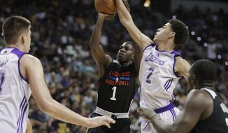 Los Angeles Lakers' Lonzo Ball blocks a shot by Los Angeles Clippers' Jawun Evans during the first half of an NBA summer league basketball game, Friday, July 7, 2017, in Las Vegas. (AP Photo/John Locher)