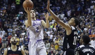 Los Angeles Lakers' Lonzo Ball shoots over Los Angeles Clippers' Brice Johnson (10) during overtime of an NBA summer league basketball game, Friday, July 7, 2017, in Las Vegas. (AP Photo/John Locher)