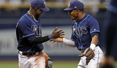 Tampa Bay Rays shortstop Adeiny Hechavarria, left, is congratulated by Mallex Smith after making a diving stop and throwing out of Boston Red Sox's Sandy Leon during the fifth inning of a baseball game Saturday, July 8, 2017, in St. Petersburg, Fla. (AP Photo/Mike Carlson)